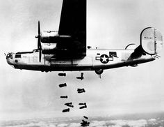 "A consolidated B-24 Liberator of the 15th A.F. releases its bombs on the railyards at Muhldorf, Germany on 19 March 1945. Bombers of the 15th A.F. are slicing vital rail lines from Vienna to Munich as the air offensive against the enemy reaches an all time high. (U.S. Air Force photo)   B-24M-1-FO S/N 44-50443 from the 727th BS, 451st BG, named ""LOW-AN-ROY"" (16). This plane was scrapped at RFC Walnut Ridge on Dec. 20,1945."