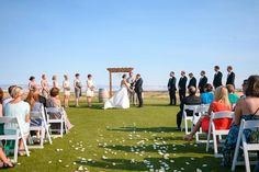 outdoor wedding ceremony with scattered rose petals and wooden arch @myweddingdotcom