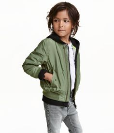 Khaki green. Lightly padded pilot jacket with a ribbed stand-up collar. Zip at front, side pockets with flap and snap fastener, sleeve pocket…