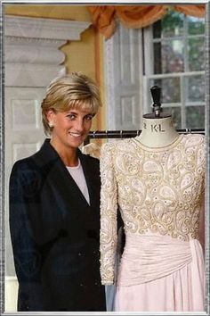 Diana poses with one of her dresses before the auction at Christie's in New York, June 1997
