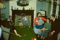 Printed colour photograph of Muriel Scagell with her children Andrea and Robin, cousins June and Johnny and Uncle Archie and Auntie Lettie playing billiards in the dining room of 1 Milverton Drive, Ickenham, Middlesex at Christmas time. The photograph was taken by Gordon Scagell in December 1958. This is a copy made from the original colour Kodachrome transparency for the Geffrye Museum in 2009, and is one item in the Documenting Homes collection (150/2010-1 to –43) from Andrea Scagell.