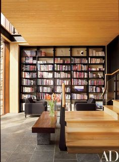 In the lower-level library, custom-made metal shelves hold Abbeville titles; the armchairs are covered in a black wool felt by Donghia | archdigest.com
