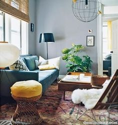 The more I look at this the more I love it - wall colour and couch are an interesting combo - lamp great touch and the mustard yellow on stool.