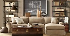 this room has great texture too. leather trunk as coffee table and blueprints framed in the background.