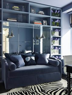 """""""Ritz-Carlton Showcase Apartment by Samantha Todhunter"""" -- I pretty much love all of this room, from that bookcase to the mirror to the color scheme! The faux zebra rug with the blue/grey is a combination that surprised and delighted me and I love the hyacinths along the window-edge with this color. -- Click through for a list of details and sources."""