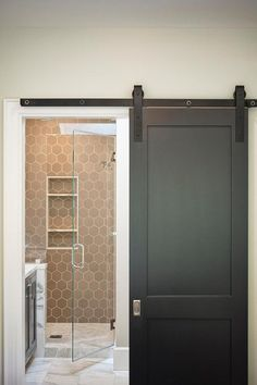 A black sliding door on rails opens to a en suite bathroom boasting a walk-in shower clad in large taupe hex tiles over a marble hex shower floor.