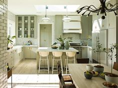 Eat in kitchen with white subway tile walls and backsplashes with dark grout, knotty wood floor, grey cabinets and drawers, an island with a marble counter top and two pendant lights