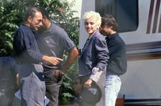 Madonna with manager Freddy DeMann, bodyguard Clay and photographer Herb Ritts on location during the filming of Open Your Heart in the Echo Park district of Los Angeles in 1986.