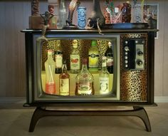 A vintage tv upcycled into a liquor cabinet with swanky leopard print fabric and tiki swag
