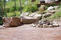 Recessed natural stone fire pit with rock seating area ...
