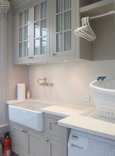 Grey cabinetry, ivory counters, farmhouse sink and room to hang delicates