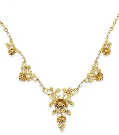 An Art Nouveau gold and seed pearl necklace - The front composed of five graduated openwork panels modelled as roses and leaves with seed pearl spacers, to a fancy link neckchain, circa 1900.