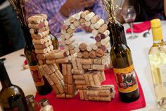 Center Piece made from collected corks and lots of hot glue. Would suggest reinforcing with a stronger glue after hot glue sets. Wine bottles labeled with photos of us and filled with clearance foliage from Michaels.