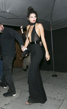 For her 20th birthday party in L.A., Jenner wowed attendees and paparazzi alike with a high-necked, plunging black jumpsuit. While the onsie was decidedly chic and dressy, beauty-wise she opted to pair her classic red lip with a quintessential post-gym top knot—wisps et al.    - MarieClaire.com