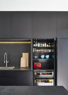 M House is a minimalist house located in Melbourne, Australia, designed by DKO. The kitchen space features blacked out custom cabinetry with a black kitchen island that allows for seating and serving. Hidden Kitchen, Kitchen Pantry, New Kitchen, Kitchen Storage, Kitchen Dining, Kitchen Decor, Kitchen Cabinets, Gray Cabinets, Kitchen Ideas