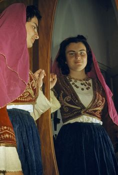 Woman modeling a Cretan costume stands beside her mirrored reflection.