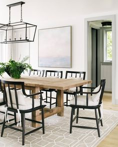 Black dining chairs paired with a reclaimed wood dining table + caged light chandelier + large art piece in the dining room Dining Chandelier, Dining Room Lighting, Black Dining Chairs, Dining Room Chairs, Dining Tables, Coffee Tables, Dining Area, Home Modern, Modern Coastal