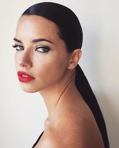 Stunning Adriana Lima with sleek ponytail and red lipstick.