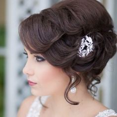 A Wonderful chignon with soft waves and curls lightly teased from it to give a romantic look. Dark eyes, deep rose lips and a pretty pink blush make a dark haired bride look stunning. The hair clip and dangling earrings are divine.