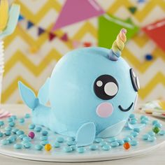 What's more magical than a unicorn? A magical narwhal of course! This adorable Narwhal Cake has swum the ocean blue in search of some birthday fun, and kids of all ages are sure to love this little guy's colorful horn and sweet smile. Made using the Wilton Ball Pan and a combination of cake and rice cereal treats, this cute denizen of the deep couldn't be happier to celebrate! Decorate your Magical Narwhal Cake with blue buttercream and fondant for a super cute dessert that's (almost) just…