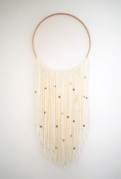 Add beads to your wall hanging for an ornamental effect.