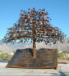 """""""The Tree of Knowledge"""" .. Bronze sculpture by Joe A. Tyler stands before the Catalina Mountains and welcomes visitors at the Oro Valley Public Library entrance"""