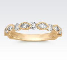 Beautiful marquise diamonds alternate with classic, round diamonds in this vintage-inspired wedding band crafted of quality 14 karat yellow gold. A total of six marquise diamonds (approx. .35 carat TW) and five round diamonds (approx. .36 carat TW) are featured admirably in this band with a total weight of approximately .71 carat.