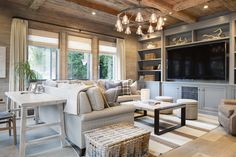 Rustic elegant living room features weathered wood planked ceiling accented with criss cross beams over wood planked walls which frame three windows layered in linen drapes and roman shades.