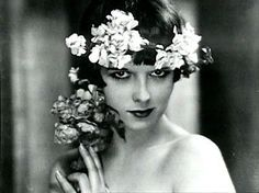 Louise Brooks, remarkable silent movie actress and remarkable bio. She was spicy, intelligent en talented. Also underestimated. Ik like this photo because of the contrast between the sweet flowers and her defiant expression