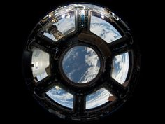 A view of Earth as seen from the Cupola on Earth-facing side of the International Space Station. Visible in the top left foreground is a Russian Soyuz crew capsule. In the lower right corner, a solar array panel can be seen.