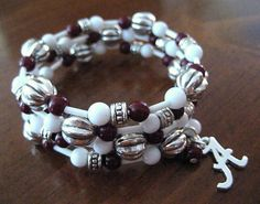 Silver-toned metal Alabama A charm accents one end of this crimson, white, and silver beaded wrap bracelet.  strong but flexible, wrap wire encircles your wrist approximately 3 times around.