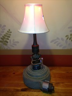 Table lamp made for fire chief. Old brass fire nozzle and cotton hose.
