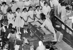 As a priest cleans the glass covering the casket of Monsignor Oscar Romero, late Archbishop of El Salvador, mourners including a group of nurses, file by, March 27, 1980, at the Metropolitan Cathedral in San Salvador. Romero was assassinated as he celebrated Mass. (AP Photo/Reed Saxon)
