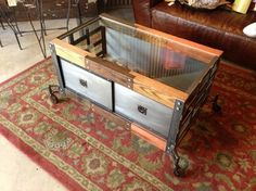 coffee tables by rogue decor co. - reclaimed barn wood beams, planed, stained, sealed and shiplap joined together. sliding bypass metal doors on both sides and woven metal sides and bottom. tempered glass top with antique cast iron casters with wood wheels.
