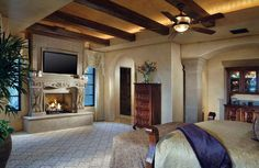 Master bedroom with stone fireplace, exposed beam ceiling and wall columns