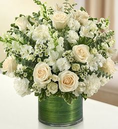 A striking, all-white arrangement of white roses, spray roses, snapdragons, alstroemeria, carnations, mini carnations, and monte casino, gathered with variegated pittosporum and spiral eucalyptus;