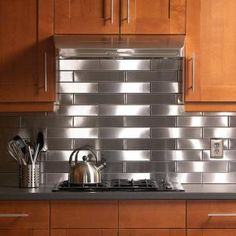 Steel, aluminum and copper tiles make dramatic, high impact kitchen backsplashes. They're also easy to install, last forever and don't require any grouting.