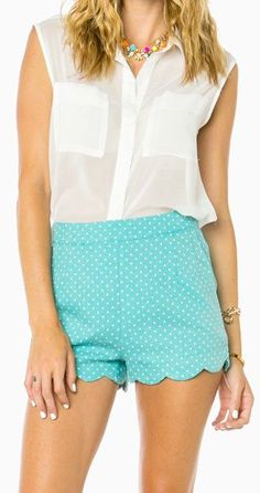 A charming polka dot print details these high waisted shorts. A scalloped hem and back zipper finish the look