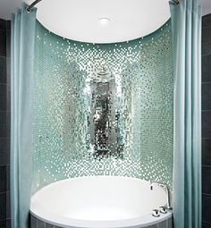 Sparkling Water  Designed by the legendary Philippe Starck, the bathtubs at the Royalton Hotel in New York are surrounded by shimmering glass tiles that reflect the aqua and slate color schemes of the room. So refreshing.