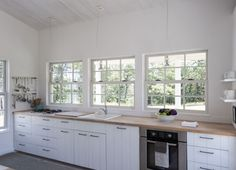 Architect Sheila Narusawa's kitchen in Cape Cod | Remodelista The custom cabinetry is all shiplap poplar, a painstaking tongue-and-groove construction borrowed from old Cape houses and painted with primer. (See The Enduring Appeal of Shiplap.) For a high/low mix, Sheila paired them with affordable butcher block counters and simple black metal squared-off drawer pulls from the hardware store.