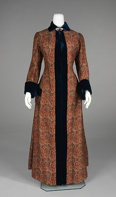 Printed wool dressing gown with midnight blue silk velvet trim, American, 1880-85. This dressing gown is an example of at-home-wear that became especially prevalent when it became acceptable to receive intimate guests in an informal manner. It is made of beautiful fabric that is more distinctive than the popular paisley patterns and it has an elegant form due to its construction details.