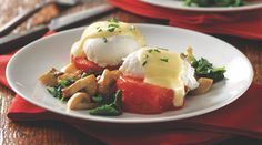 Poached eggs and a yogurt-based Hollandaise sauce are piled atop roasted tomatoes instead of English muffins for a tasty, low-carb meal.