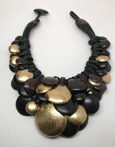 Fabulous Gerda Lynggaard Monies Leather, Gold Leaf, African & Ebony Wood Necklace  Six layers of different size of well crafted coins, very good condition, Signed, Just stunning!  It measure 18 long and 5 at the widest, comes with Monies pouch.  The pictures are part of the description so
