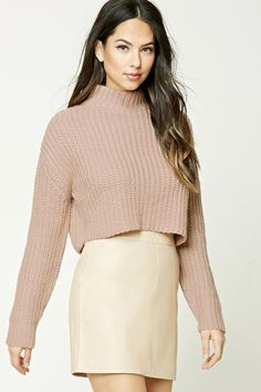 A chunky knit sweater featuring a turtleneck, dropped long sleeves, and a cropped silhouette.