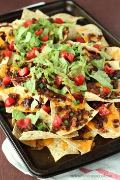 BBQ Bacon Cheeseburger Nachos: the best nachos you've ever had! Barbecue sauce, ground beef, bacon, cheddar cheese, green onions and all the burger toppings you want. Perfect for movie night or game day! www.thereciperebel.com