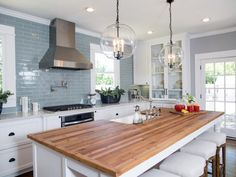 I love the white cabinets, blue subway tile and butcher block island.