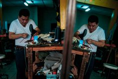 PhotoNotes - FotoNotas  Jose Alfredo repairs a pair of shoes in his shop inside Santa Ana's marketplace. He makes custom leather shoes as well as repairs, his family used to run a family-owned shoe making factory but one of the reasons it closed down was due to the free trade agreement with China, many Salvadorans started buying shoes made in China which are cheaper than leather shoes but of lower quality.