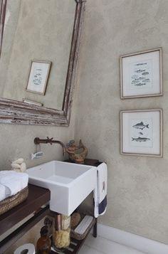 Lavabo na casa de praia com parede em cimento queimado. Projeto de Paola Ribeiro