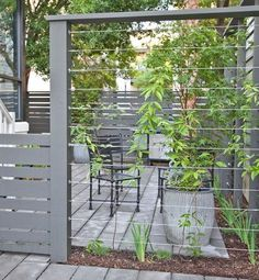 Cable wires mounted between fence posts create a sturdy support for climbing plants. Over time the plants will fill in the area, providing privacy for your patio. #deckbuildingdiy
