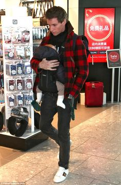 Daddy daycare: Eddie Redmayne looked every inch the regular doting dad as he carried his baby daughter, Iris Mary, six months, through London's Heathrow Airport on Wednesday